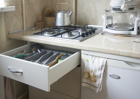 Fragment of kitchen with gas cooker, kettle and drawer with kitchen utensils Stock Photo