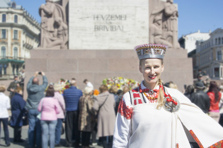 Latvia, Riga-may 4.2017:  Portrait of a girl in a Latvian national costume against the background of the Freedom Monument in Riga on the Day of Restoration of Independence of Latvia Editorial