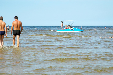 Europe, Latvia, Jurmala-- July 13.2006: People bathe and swim on a catamaran at the coast of the Gulf of Riga of the Baltic Sea. Editorial