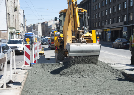 Repair of an asphalt covering on the brisk city street. Operation of the grader.