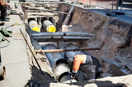 Laying sewer and gas pipes under the ground in a city street. Work welder.