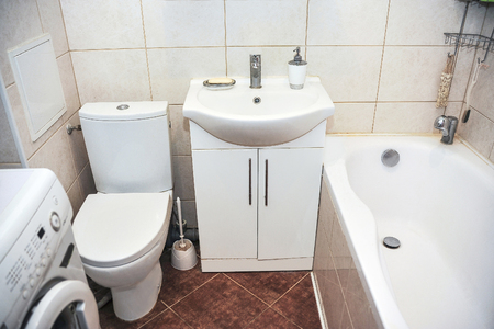 Bathroom In A Small Apartment With Toilet, Sink And Washing Machine ...