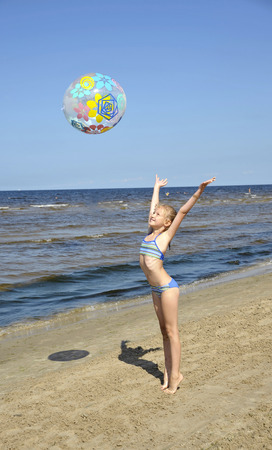 The girl plays with a ball on seacoast a beach in Jurmala (Latvia). Stock Photo