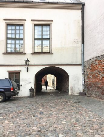 Europe, Latvia,  Riga. Entrance courtyard with an arch and cobblestone pavement in old Riga(vertical).