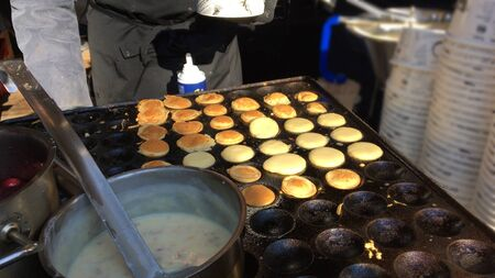 The process of making small pancakes on the street from the dough on an electric stove with molds.