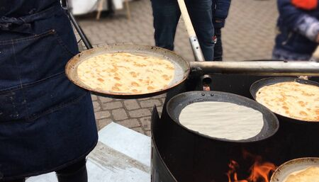 Process of preparation and frying of pancakes independently on the street in maslenica and Easter in pans.