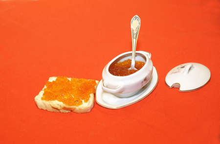 Red caviar in a bowl with a spoon and on a sandwich isolated on red. Banco de Imagens