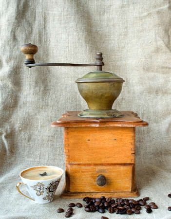 Ancient coffee grinder with grains and a cup of coffee