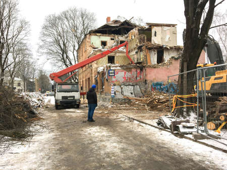 Demolition of an old, dilapidated residential building on a city street