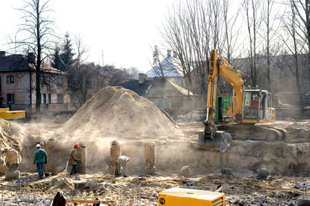 Home construction begins. Digging a pit with an excavator and the work of builders.