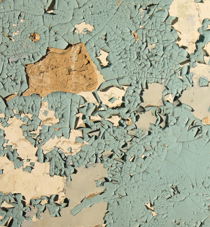 foundation cracks: Old cracked paint blue on top of a white wall, in some places completely flown away, side lighting sunlight Stock Photo