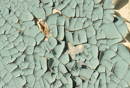 foundation cracks: Old cracked paint blue on top of a white wall, side lighting sunlight Stock Photo