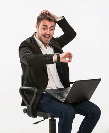 his: Tired manager sitting on a chair working with a laptop in a panic looking at his watch on his right hand holding his head with his left hand. Studio, white background.