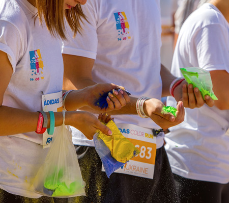 km: Kyiv, Ukraine, - Augus 14,2016. Kyiv color run. Run 5 km from the colors of Holi. Participants of the race color run woman and man are holding a paint Holi.