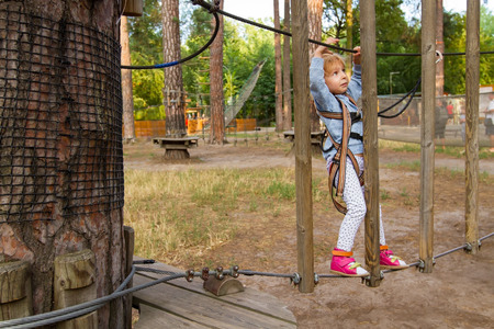 fall arrest: Three-year girl the blonde with a personal fall arrest system obstacle in the rope town.