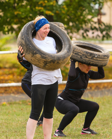 Kyiv, Ukraine - October 082016. Outdoor CrossFit training, preparation for competition Race Nation. Autumn. Girl trying to lift a tire over her head.