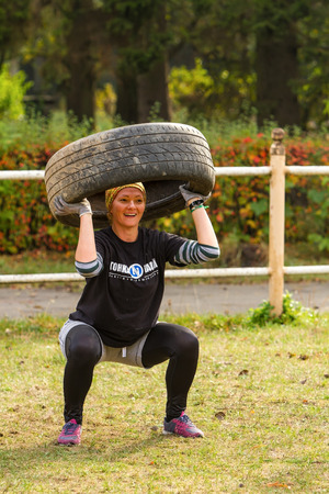 Kyiv, Ukraine - October 082016. Outdoor CrossFit training, preparation for competition Race Nation. Autumn. The girl crouches with the tire and smiling.