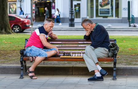 play date: Lviv, Ukraine - July 15, 2016. Two men sitting on a bench in a park playing chess. Men play chess. Editorial