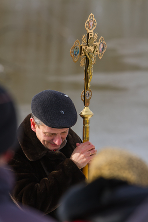 Rovzhi, Ukraine - January 19, 2014 Christian holiday Baptism in the Orthodox calendar. The man bowed his head in prayer holding orthodox cross with the crucifixion of Jesus. Editorial
