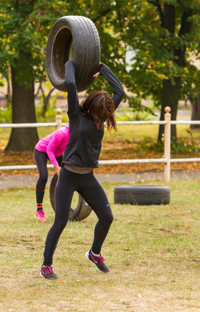 squatting down: Kyiv, Ukraine - October 08, 2016. CrossFit training, preparation for competition Race Nation.  Autumn. Girl raises the tire over his head and forcefully throwing her to the ground.