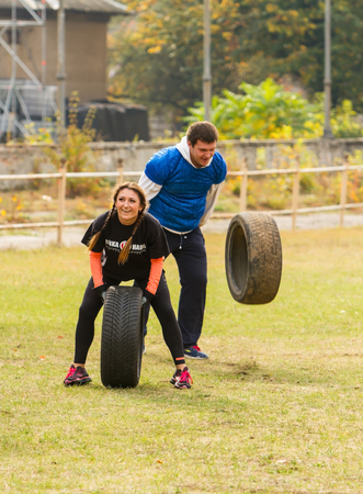 """levantar peso: Kiev, Ucrania - 08 de octubre de 2016. CrossFit entrenamiento, preparación para la competición """"Nación de carreras."""" Otoño. Chica y el chico en el neumático levantar la cabeza y con fuerza arrojándola al suelo."""