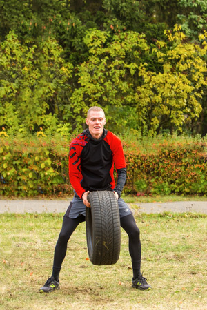 squatting down: Kyiv, Ukraine - October 08, 2016. CrossFit training, preparation for competition Race Nation.  Autumn. Guy raises the tire over his head and forcefully throwing her to the ground.