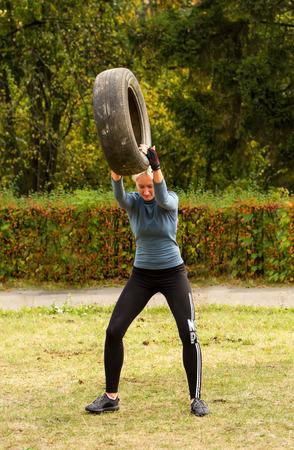 levantar peso: Kiev, Ucrania - 8 de octubre. 2016. entrenamiento de la calle CrossFit entrenamiento. La niña levanta la rueda sobre su cabeza y la tira al suelo con fuerza.