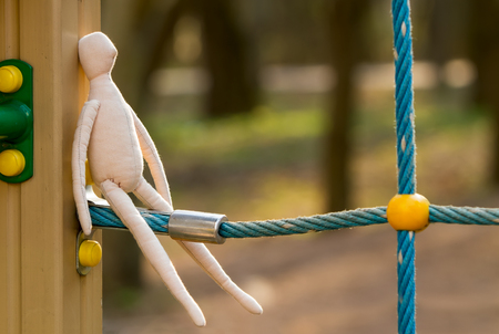 The sewn faceless doll in the profile sits on a blue rope, the construction of a playground. Stock Photo