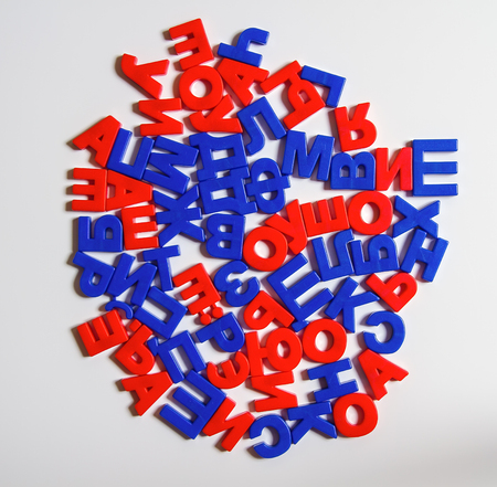 upbringing: Russian language. Plastic letters with a magnet in a chaotic order are arranged in the form of a circle. Cyrillic. Stock Photo