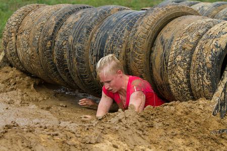 La niña se arrastra en el barro, superando emocionalmente el obstáculo hecho de neumáticos. Foto de archivo