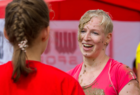 The girl smiles and emotionally communicates after completing the race along the route with obstacles.