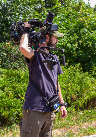 Assistant cameraman with wireless focus control keeps the camera on his shoulder before shooting.