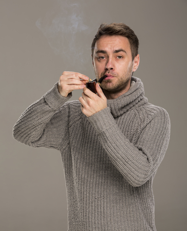 man lights a pipe with a match in the studio on a gray background
