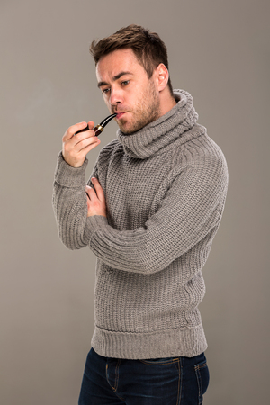 in the studio on a gray background, a man in a gray sweater stands thoughtfully, crossing his arms at the chest level, with a pipe in his mouth. Фото со стока