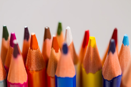 snapshot of pencils of different colors on a gray background, with a small depth of field, macro.