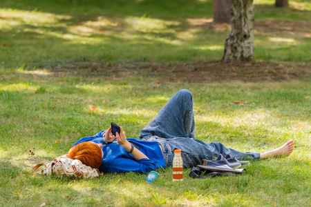 young red-haired girl lying on the grass in the park and looking into the smartphone