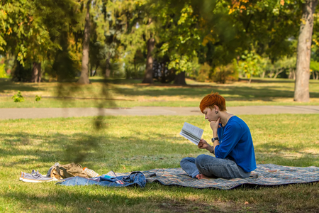 Redheaded girl reading a book on a glade in the park.