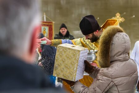 Rovzhi, Ukraine - January 19, 2014. A priest takes money from parishioners, 20 hryvnias, next  a woman is holding a donation basket for the church. Christian holiday Baptism.