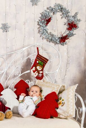 baby with fingers of his left hand in his mouth lying on a sofa among pillows and toys on New Year's theme Archivio Fotografico - 133230732
