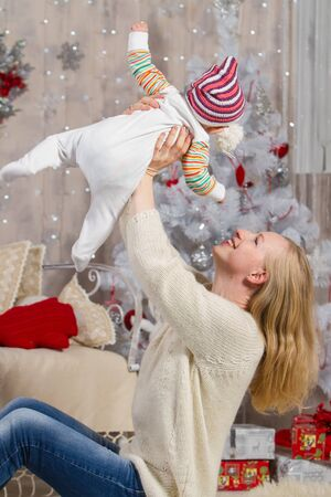 girl holds the child in her arms high above her head, against the background of a white Christmas tree with toys and gift boxes sitting on the carpet on the floor Archivio Fotografico - 133139023