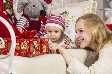close-up, mother and her baby in a knitted hat lying on their stomach on the couch are looking at a gift box, on a Christmas theme Archivio Fotografico - 133672216