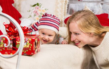 close-up, mother and her baby in a knitted hat lying on their stomach on the couch are looking at a gift box, on a Christmas theme Archivio Fotografico - 133672295