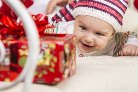 close-up of a smiling baby in a knitted hat lying on his stomach on the sofa among gifts and toys on New Year's theme Archivio Fotografico - 133672297