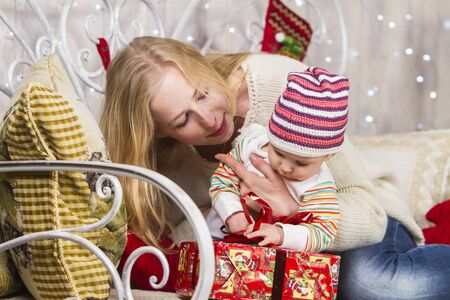 A girl holds a child in her arms while sitting on a sofa near toys and gifts on a Christmas theme, the baby holds on to a bow on a gift box. Archivio Fotografico - 133672331