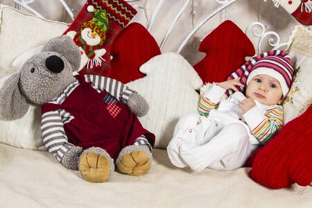 baby in a knitted cap lying on the sofa among pillows and toys on New Year's theme Archivio Fotografico - 133672356