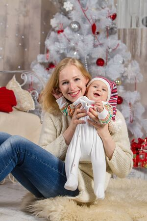 girl holds a child in her arms on a background of a white Christmas tree with toys and gift boxes sitting on a carpet on the floor Archivio Fotografico - 133672353