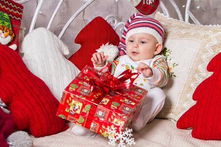 baby and christmas, a baby in a knitted hat lies on his back on the couch among pillows and toys on the New Year theme, he has a gift box in his legs Archivio Fotografico - 133672382