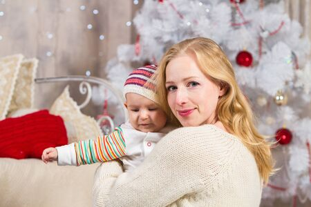 girl holds a child in her arms on a background of a white Christmas tree with toys, sitting on a carpet on the floor Archivio Fotografico - 133672427