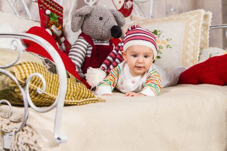 baby and christmas, the child lies on his stomach on the couch and looks away, around toys and gifts on a New Year's theme, a gray mouse is behind the child's back. 2020 year of the mouse Archivio Fotografico - 133672429