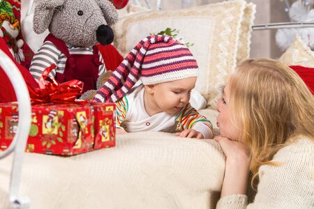 mother looks at her child lying on his stomach on the couch around toys and gifts on New Year's theme, the child looks at mother, behind the child's back is a gray mouse toy Archivio Fotografico - 133672475